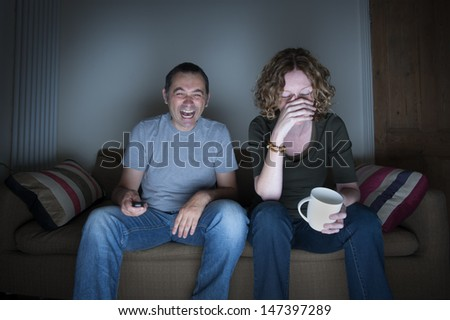 couple watching television laughing and embarrassed - stock photo