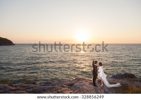 Couple watching the sunset On the Cliff by the Sea Romantic scene - stock photo