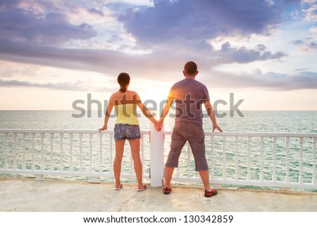 Couple watching together sunset at the ocean - stock photo