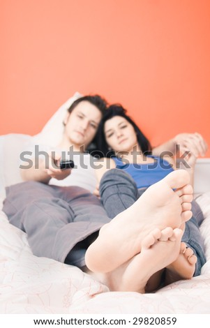 Couple watching TV from their bed - stock photo
