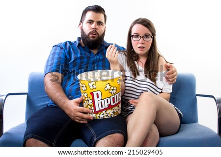 Couple watching TV on the couch and eating pop corn