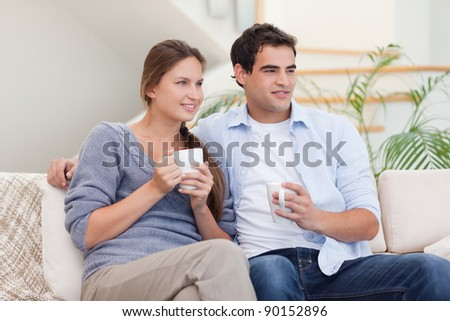 Couple watching TV while drinking tea in their living room - stock photo