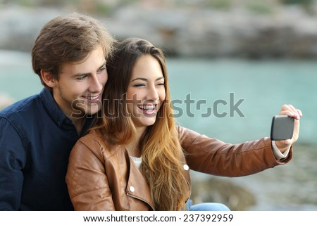 Couple watching videos in a smart phone on holidays with the beach in the background