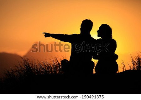 Couple watching whales at sunset on the beach.  - stock photo