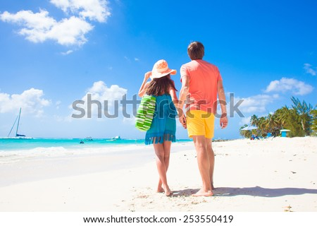 Couple wearing bright clothes on a tropical beach on Barbados - stock photo