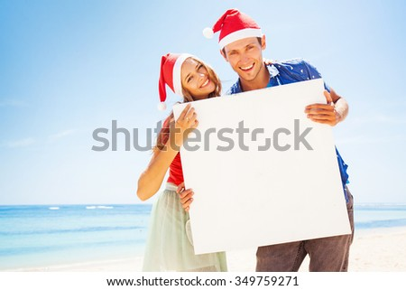 couple wearing christmas santa hats on a beach holding blank poster - stock photo