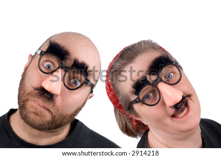 Couple wearing fake nose and glasses with mustashe and eyebrows over a white background - stock photo