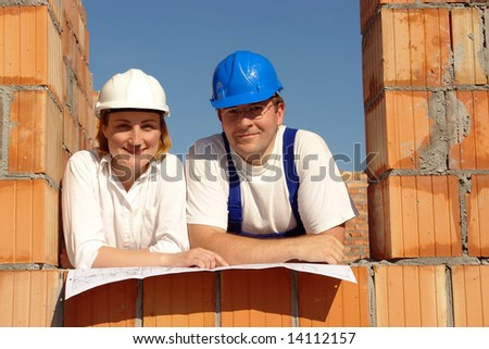 Couple wearing hard hats posing in their future house window opening resting on building plan - stock photo