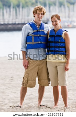 Couple wearing life jackets at beach - stock photo