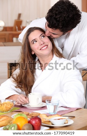 Couple wearing matching bathing robes in kitchen - stock photo