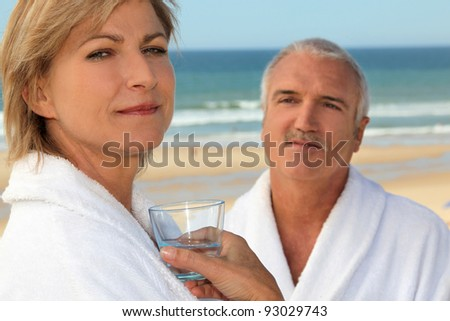 Couple wearing matching robes outdoors - stock photo