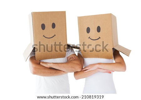 Couple wearing smiley face boxes on their heads on white background - stock photo