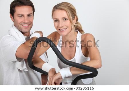 Couple wearing sportswear stood by exercise bike - stock photo