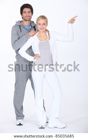 Couple wearing tracksuits pointing off camera - stock photo
