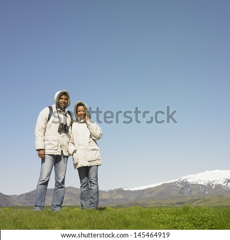 Couple wearing winter jackets standing with mountains in background