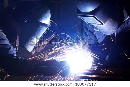 Couple welders and bright sparks. Construction and production - stock photo