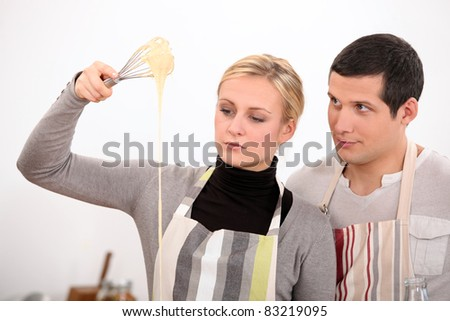 Couple whisking mixture - stock photo