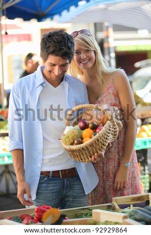 Couple with a basket at market - stock photo