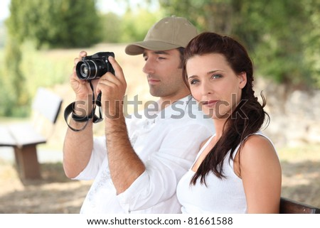 Couple with a camera in the countryside - stock photo