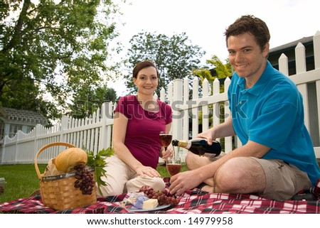 Couple with a picnic spread with wine, cheese and bread.  They are smiling and facing the camera. Horizontally framed shot. - stock photo