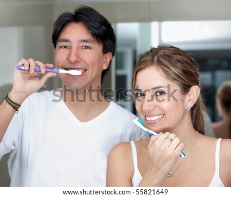 Couple with a toothbrush brushing their teeth and smiling - stock photo