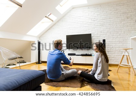 Couple with a tv remote control at home - stock photo