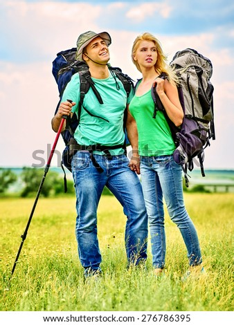 Couple with backpack  summer outdoor. Green grass. - stock photo