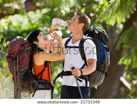 Couple with backpacks drinking water - stock photo
