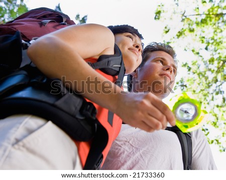 Couple with backpacks looking at compass - stock photo