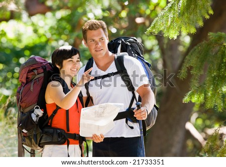 Couple with backpacks looking at map - stock photo