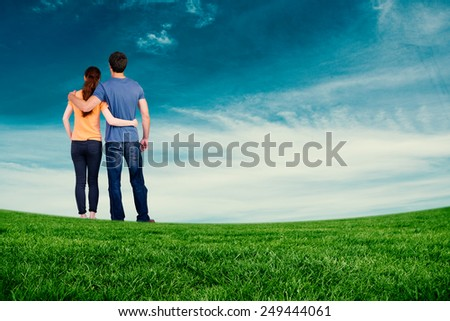 Couple with backs to camera against blue sky - stock photo