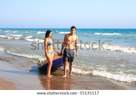 Couple with boat walking at  the sea.