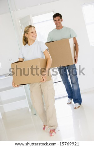 Couple with boxes moving into new home smiling - stock photo