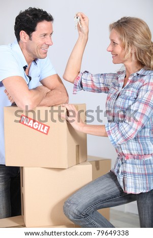 Couple with boxes smiling - stock photo