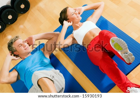 Couple with brightly colored clothes doing sit-ups in the gym - stock photo