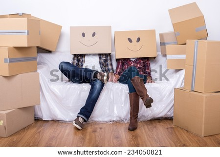 Couple with cardboard boxes on their heads with smiley face are sitting on floor after the moving house. - stock photo