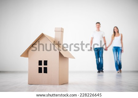 Couple with cardboard house - stock photo