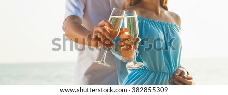 Couple with champagne glasses on the beach. Banner.  - stock photo