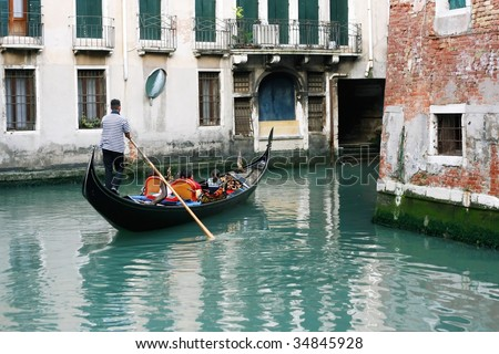 Couple with child having a romantic ride down a canal in a gondola (Venice, Italy)