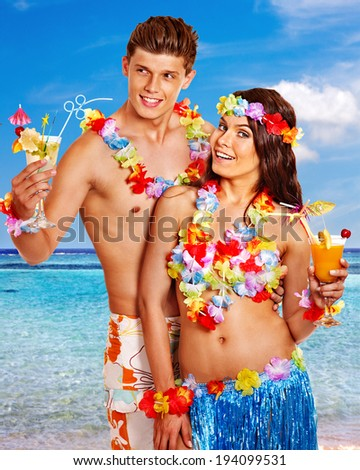 Couple with cocktail at Hawaii wreath beach. Summer outdoor.