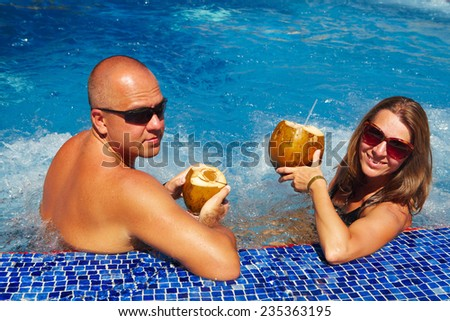 Couple with coconut drink relaxing in hot tub. - stock photo