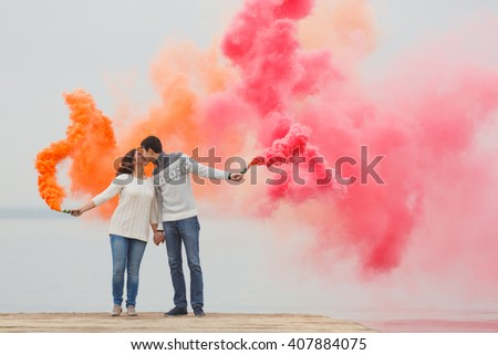 couple with color smoke on beach - stock photo
