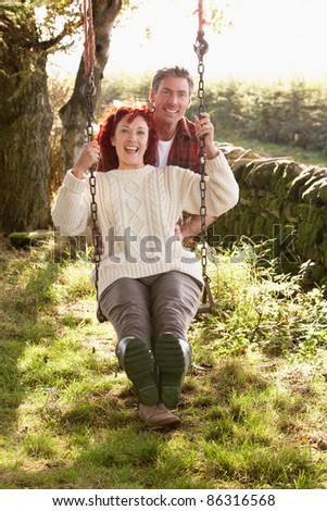 Couple with country garden swing - stock photo