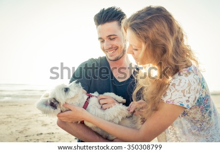 Couple with cute dog spending time on the beach. young man holding his dog with arms and stroking him