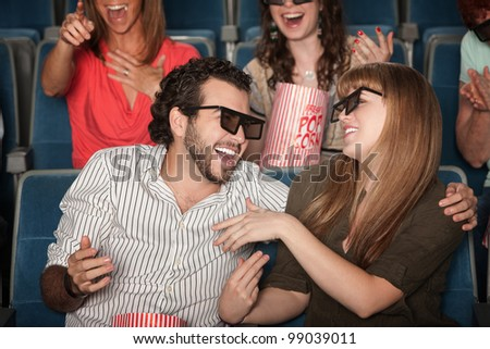 Couple with 3D glasses in theater laughing together - stock photo