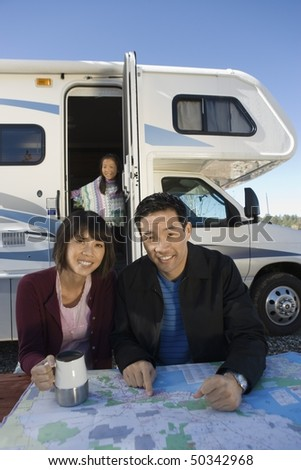 Couple with daughter looking at map on picnic table outside RV - stock photo