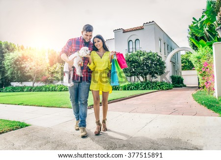 Couple with dog and real estate in the background - Rich people lifestyle - Cheerful couple in front of modern house - stock photo