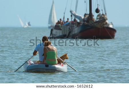 couple with dog rowing towards the shore - stock photo