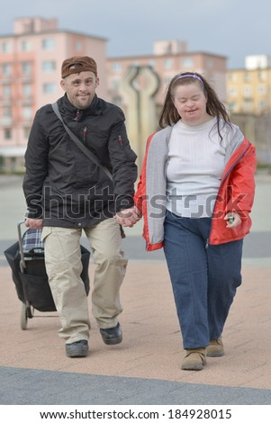 couple with down syndrome carry luggage - stock photo