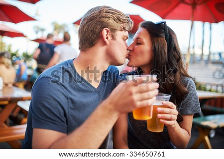 couple with draft beers kissing at outdoor pub or bar patio shot with selective focus - stock photo